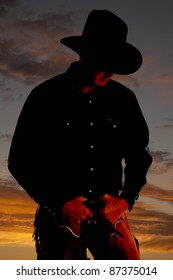 A cowboy is highlighted in the sunset and is looking down.