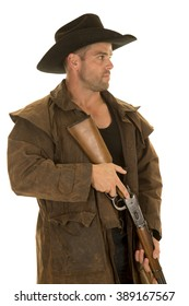 A cowboy in his duster holding on to his rifle looking serious.