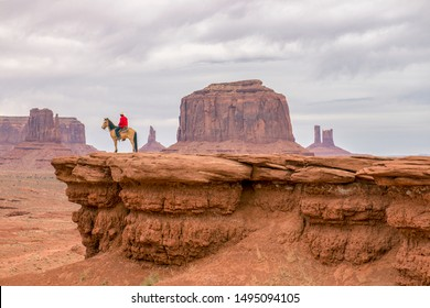 A cowboy and his horse overlook a valley in the southwest