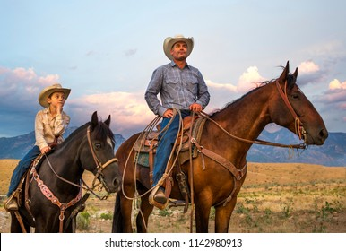 A Cowboy and his son on horseback looking over their ranch lands
