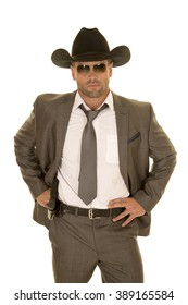 A cowboy in his suit holding on to his pistol on his hip.
