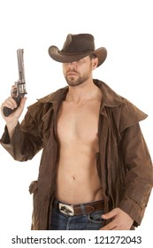 A cowboy holding up his gun with a serious expression on his face.