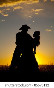 A cowboy is holding a woman in the sunset and dipping her.