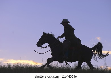 Cowboy  horseback riding against early sky