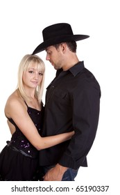 A cowboy looking down at his woman with love in his eyes, she is beautiful in her dancer outfit