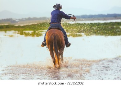 Cowboy man riding across with river