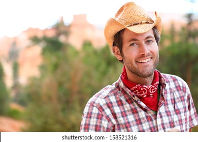 Cowboy man smiling happy wearing hat in rural USA. Male model in american western countryside landscape nature on ranch or farm, Utah, USA.