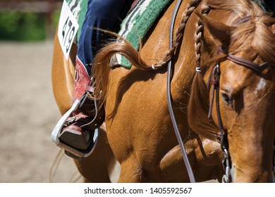 The cowboy on a chestnut horse in western style: cowboy's legs in in leather stirrups closeup