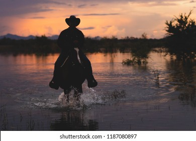 Cowboy on horseback on water and mountain background . ranch