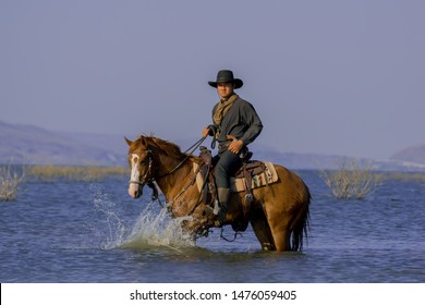 Cowboy on horseback.Cowboy riding horse and running on river.