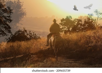 A cowboy on the trail at sunset.