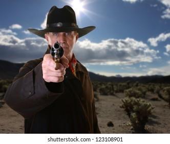 Cowboy pointing gun with selective focus on gun against desert background