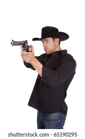 A cowboy pointing his gun and checking his aim before he shoots.