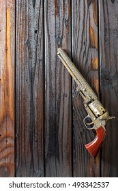 Cowboy Revolver Gun On Vertical Distressed Wood Background With Copy Space.
