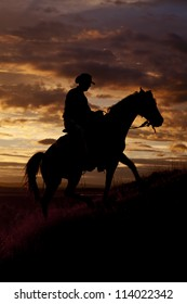 A cowboy is riding his horse up a hill in the sunset.
