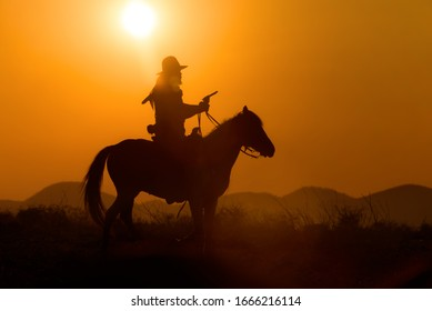 Cowboy riding a horse carrying a gun in sunset with mountain
