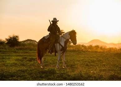 Cowboy riding horses silhouette in sunset