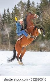 Cowboy riding rearing horse.