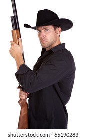 A cowboy with a serious expression on his face holding his rifle.