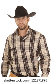 A cowboy showing his serious side with his plaid shirt and black hat on.