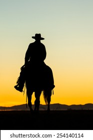 Cowboy silhouette on horse after sunset