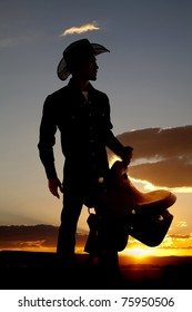 A cowboy is silhouetted in the sunset holding a saddle.