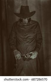 Cowboy Skeleton. Dark photo of an evil cowboy skeleton standing with hands on belt.