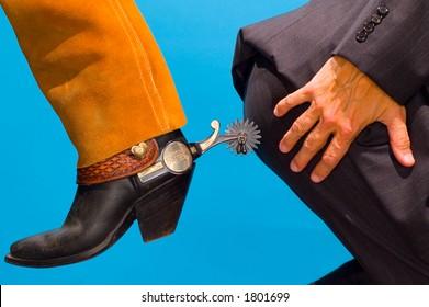 cowboy spurring business man's butt