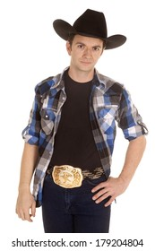 A cowboy is standing with his hand on his hip wearing a big black hat.