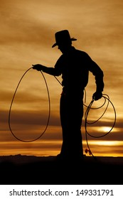 A cowboy is standing in the sunset with a rope in his hands.