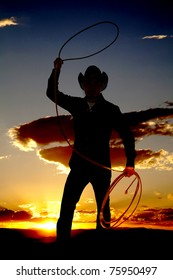 A cowboy is standing in the sunset twirling a rope