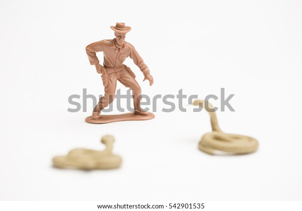 Cowboy threatened by two snakes