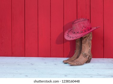 Cowboy women's boots, hat on a red wooden background