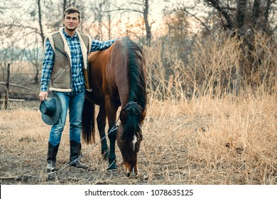 Cowboy working his horse in the field. Warm goldem autumn day. Beautiful sunset. Man weared in blue jeans, skirt in a cage, cowboy boots and hat.