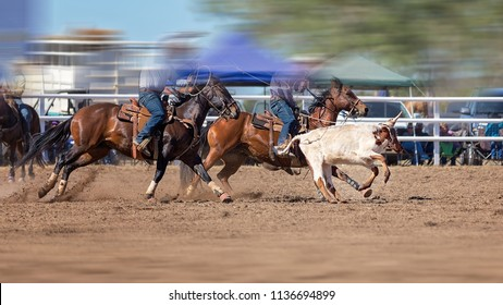 Cowboys competing in a team calf roping event at an Australian country rodeo