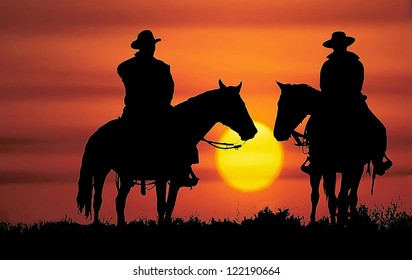 Cowboys, on horseback, silhouetted by the setting sun