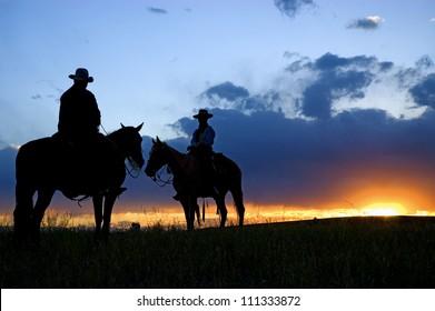 Cowboys on horseback as sun rises