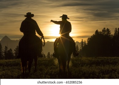 Cowboys riding across grassland with mountains behind, early morning, British Colombia, Canada