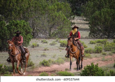 Cowboys riding horses in desert with a guns in their hands. concept  train robbery.
