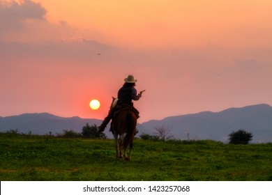Cowboys are riding horses silhouette in sunset with mountain scene for cowboy group annual meeting in Pakchong, Nakhonratchasima, Thailand taken on  04/29/2019