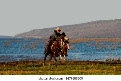 Cowboys are riding horses silhouette in sunset