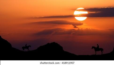 Cowboys riding at sunset