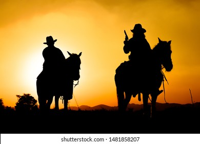 cowboys sihouette on horse with sunset