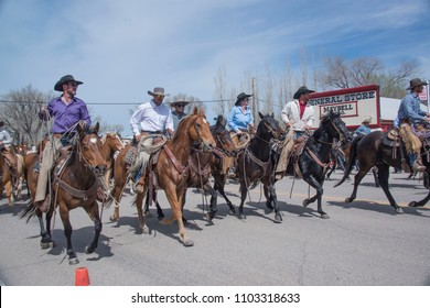 Cowboys and wranglers of Sombrero Ranch ride their horses down main street of Maybell, CO during annual Great American Horse Drive parade