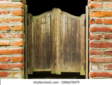 Cowboy-style wooden doors belonging to the far west with two brick columns on the sides