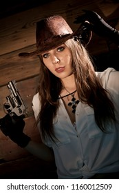 Cowgirl armed with revolver holding hat - studio shoot