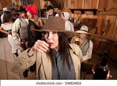 Cowgirl with bottle sipping whiskey from a shot glass
