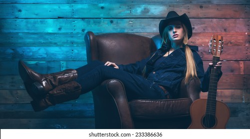 Cowgirl country singer with acoustic guitar. Sitting on leather chair. Wearing blue jeans and brown hat. In front of wooden wall.