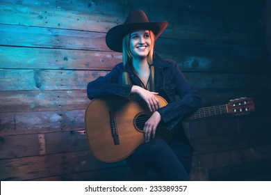 Cowgirl country singer with acoustic guitar. Wearing blue jeans and brown hat. In front of wooden wall.