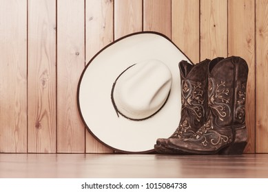 cowgirl embroidered boots and white hat on wooden background - text space